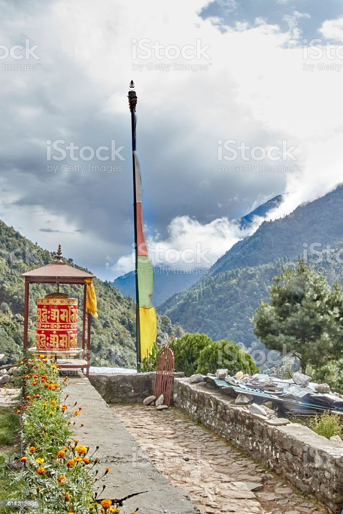 Prayer Wheel and Flag with Storm Approaching, Nepal stock photo