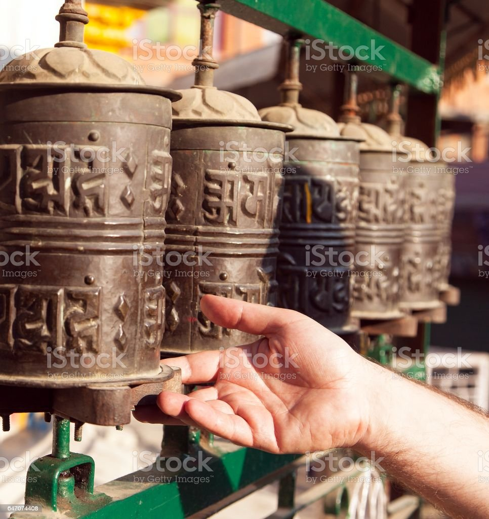 Prayer wheels and a hand stock photo