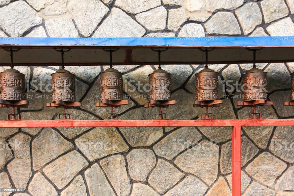 Prayer wheels with stone wall background in buddhism temple in countryside of Nepal stock photo