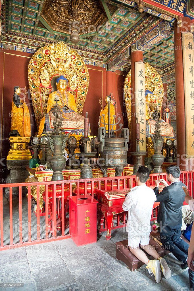 Prayers in front of Buddha statues in YongHe temple stock photo