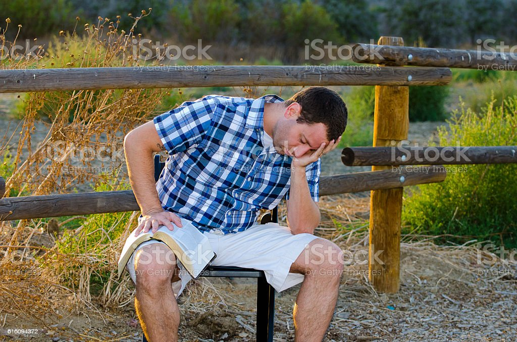 Praying alone outdoors with a Bible stock photo