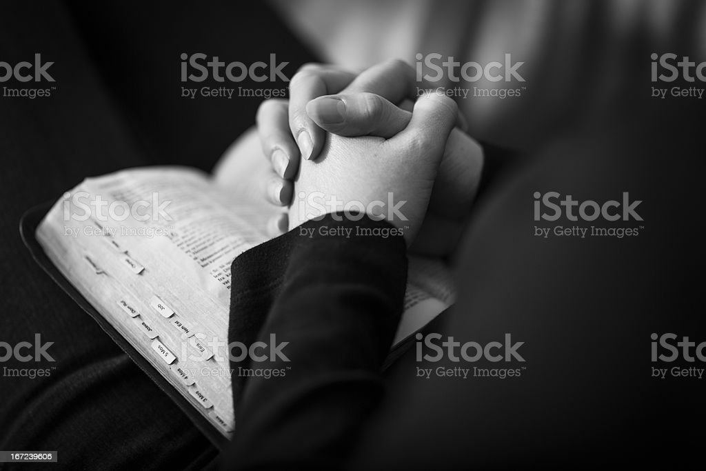 Praying and Folding Hands over a Bible royalty-free stock photo