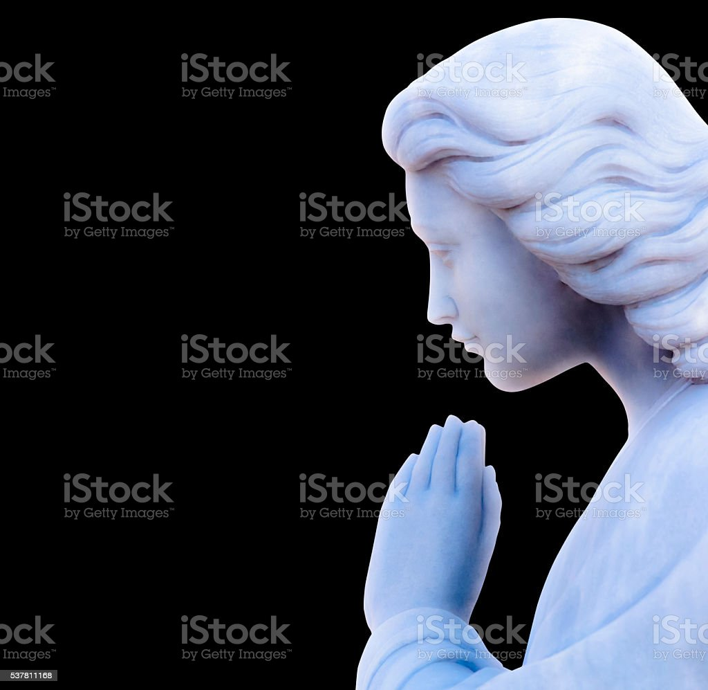 Praying angel, marble statue isolated on black background, copy space stock photo
