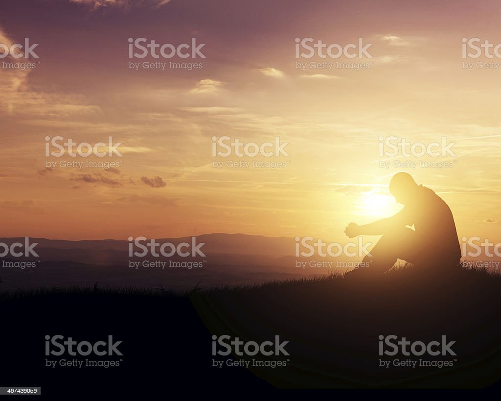 Praying at sunrise stock photo