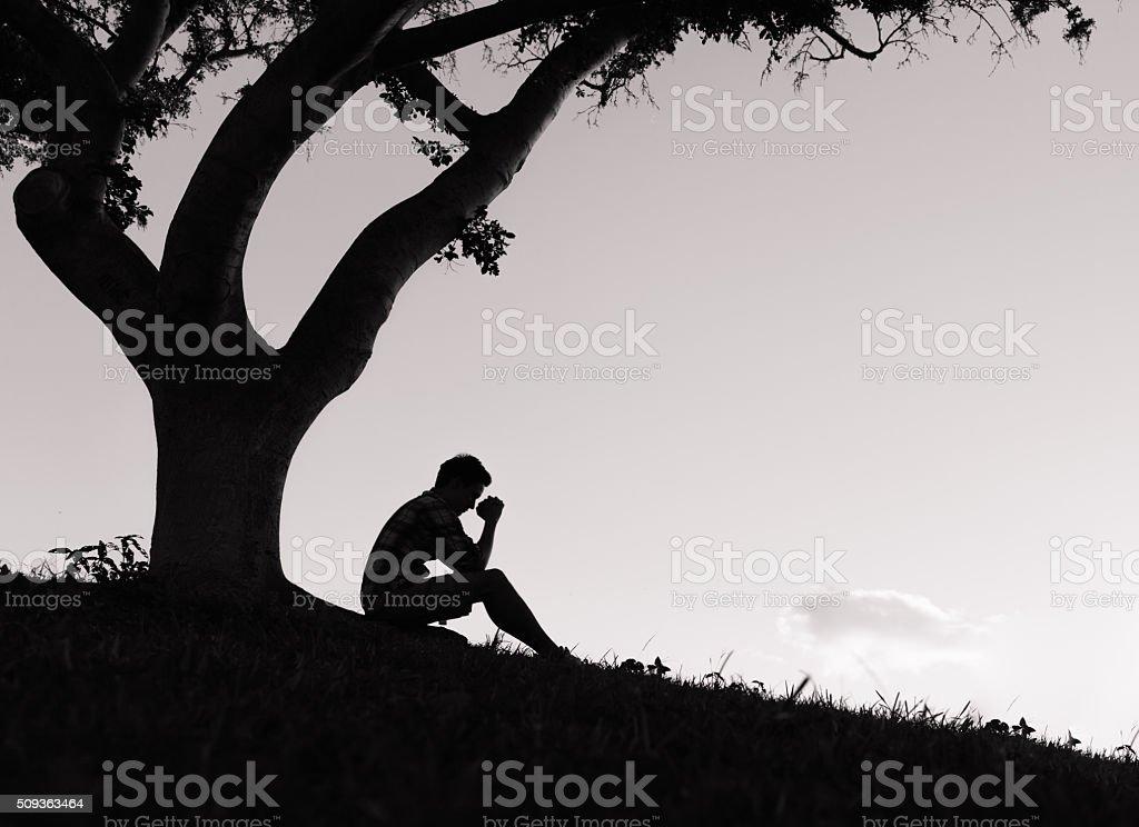 Praying at sunset stock photo