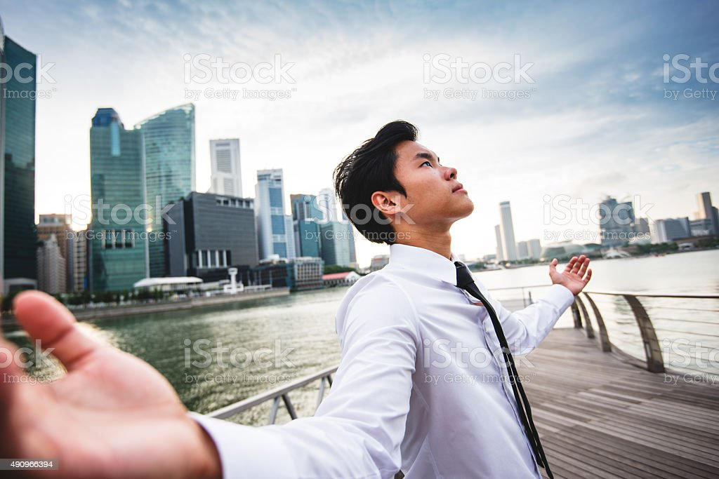 praying business man against the skyscraper in singapore stock photo
