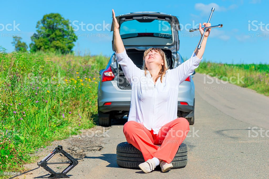 praying female driver sitting at the wheel near the car stock photo