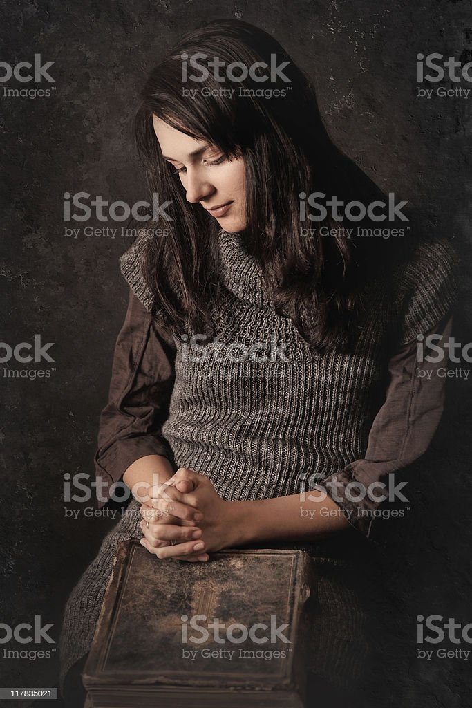 Praying girl with a large old Bible royalty-free stock photo