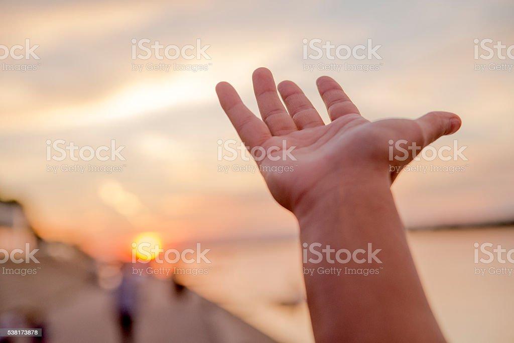 Praying hands, Hand of woman reaching to towards sky stock photo