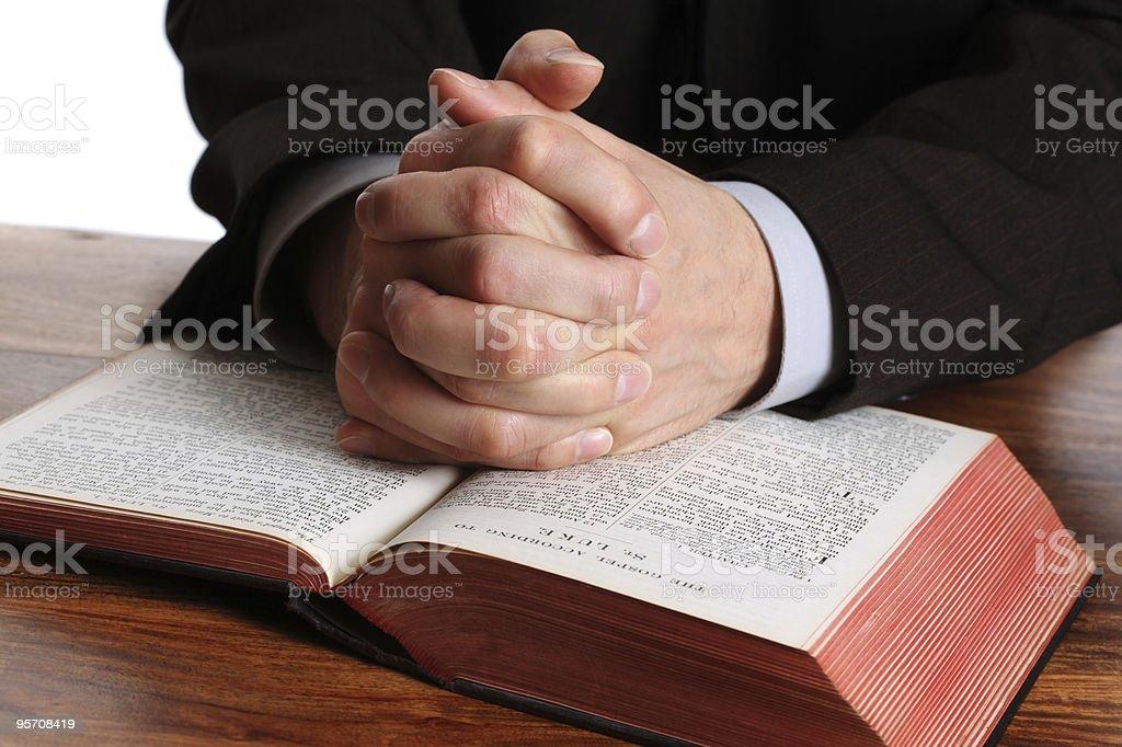 Praying hands on an open bible stock photo