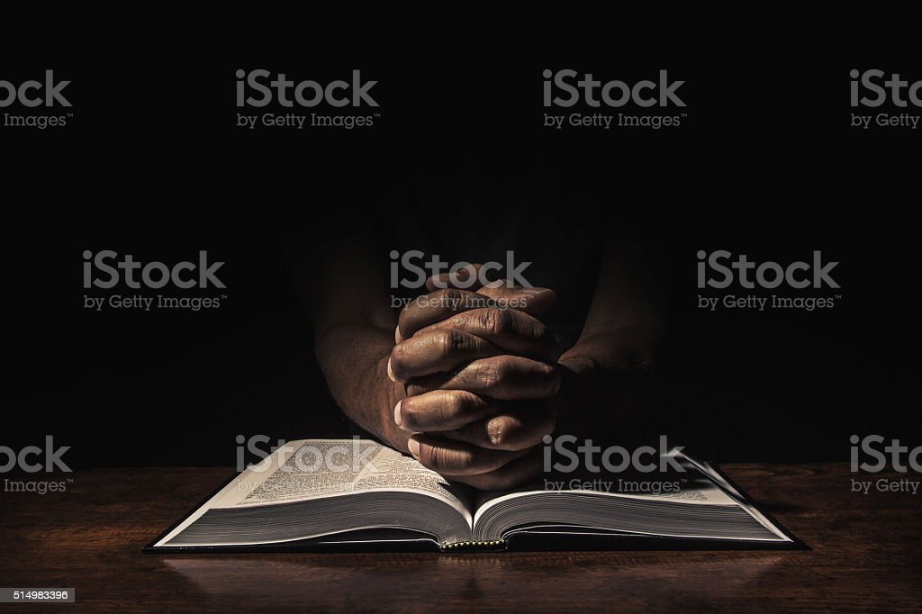 Praying in the dark stock photo