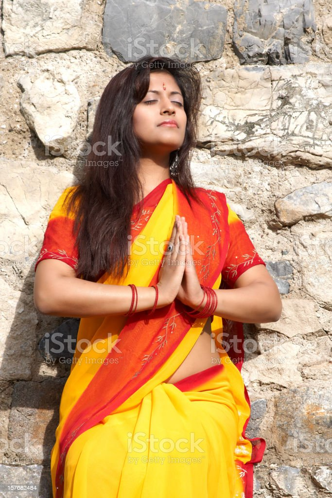 praying indian woman with a colorful sari royalty-free stock photo