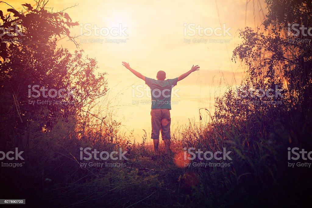 Praying Man silhouette on sunset background stock photo