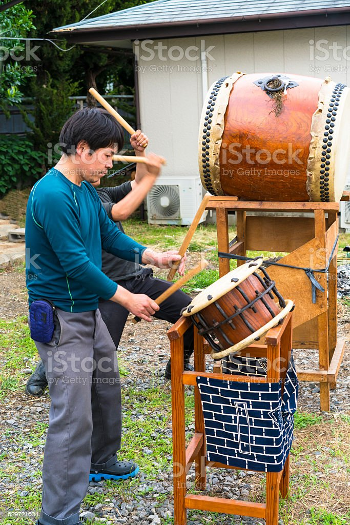 Praying men on traditional Japanese drum Taiko, Tsukuba, Japan stock photo