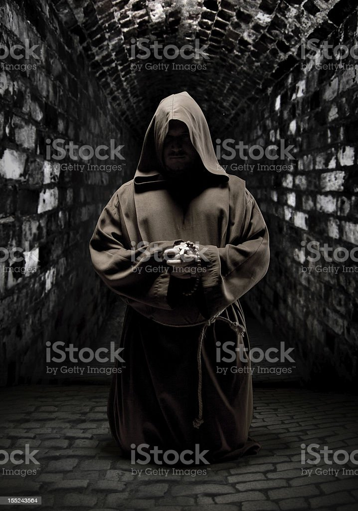 Praying monk in dark temple corridor stock photo