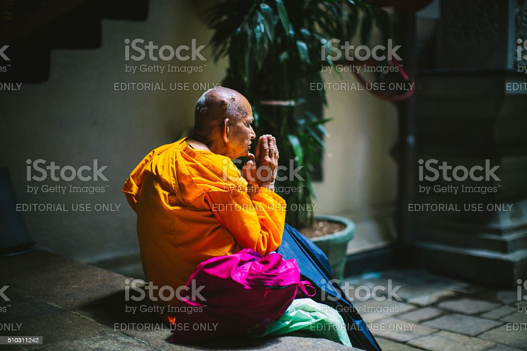 Praying monk in the temple of the tooth, Sri lanka stock photo