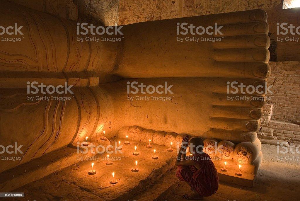 Praying novice monk in Myanmar stock photo