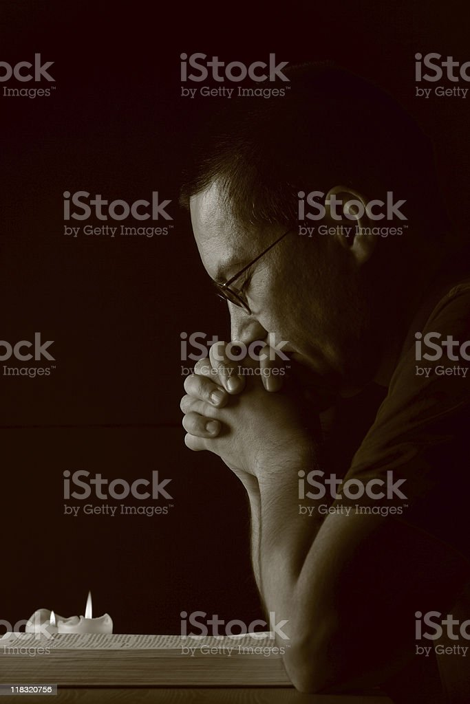 Praying over Bibel with Burning Candles Lowlight stock photo