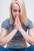 Praying, pensive, wistful, concentrated, young, blonde woman with eyes closed.