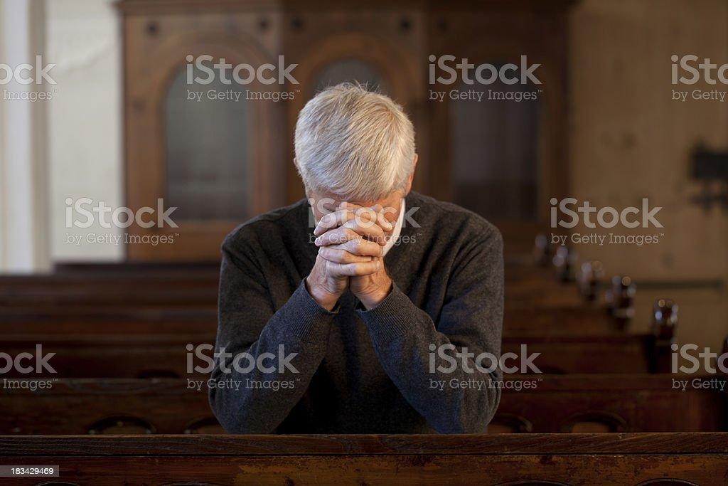 Praying senior man in church royalty-free stock photo