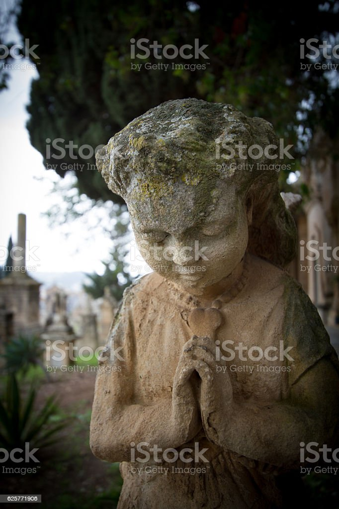 Praying Stone Angel in Cemetery with Folded Hands stock photo