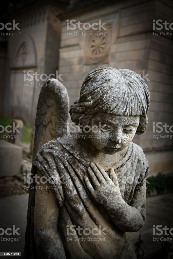 Praying Stone Angel in Cemetery with Hand on Heart stock photo
