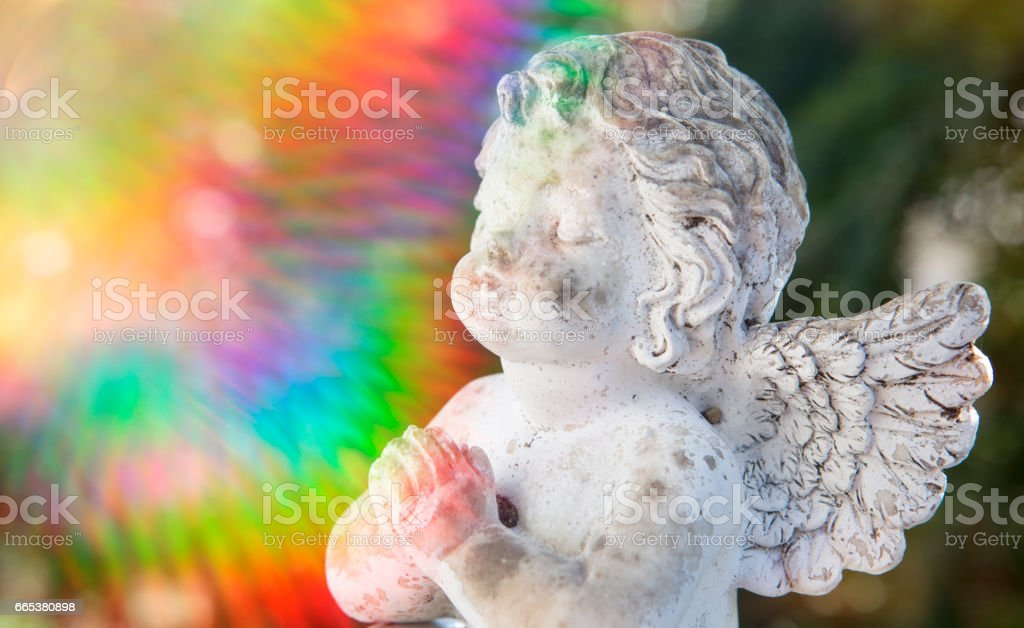 praying stone angel with colorful sunbeam stock photo