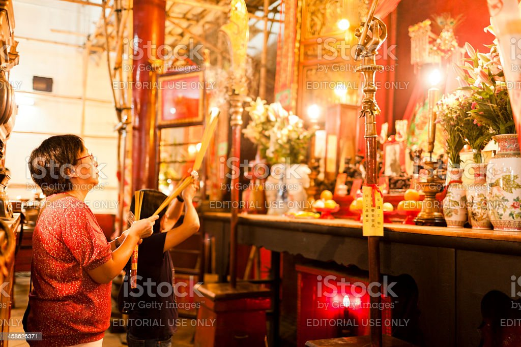 Praying woman with incense sticks royalty-free stock photo