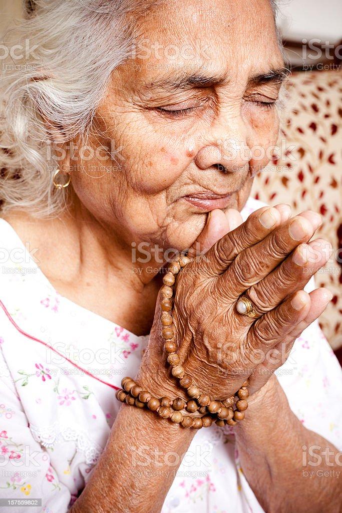 Praying wrinkled hands of Senior Indian Spiritual Woman royalty-free stock photo