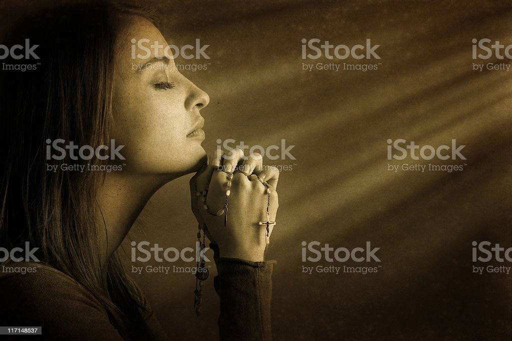 Praying young woman in divine light stock photo
