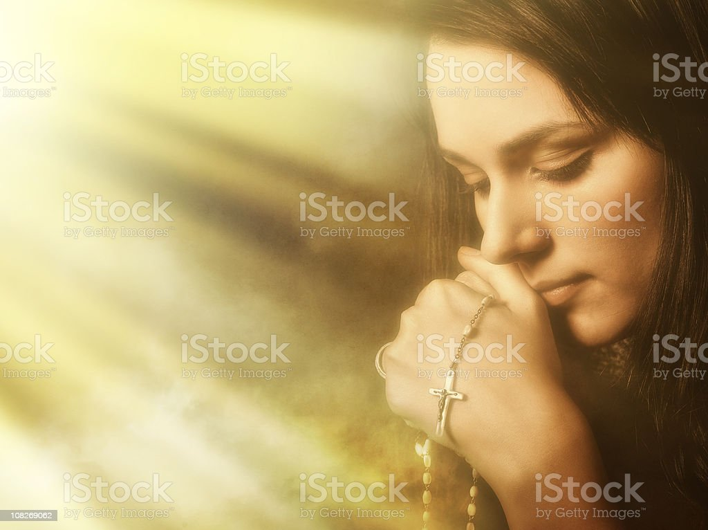 Praying young woman in light and incense smoke stock photo