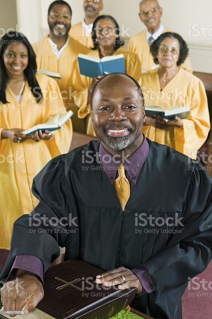 Preacher With Bible While Choir Standing In Background At Church stock photo