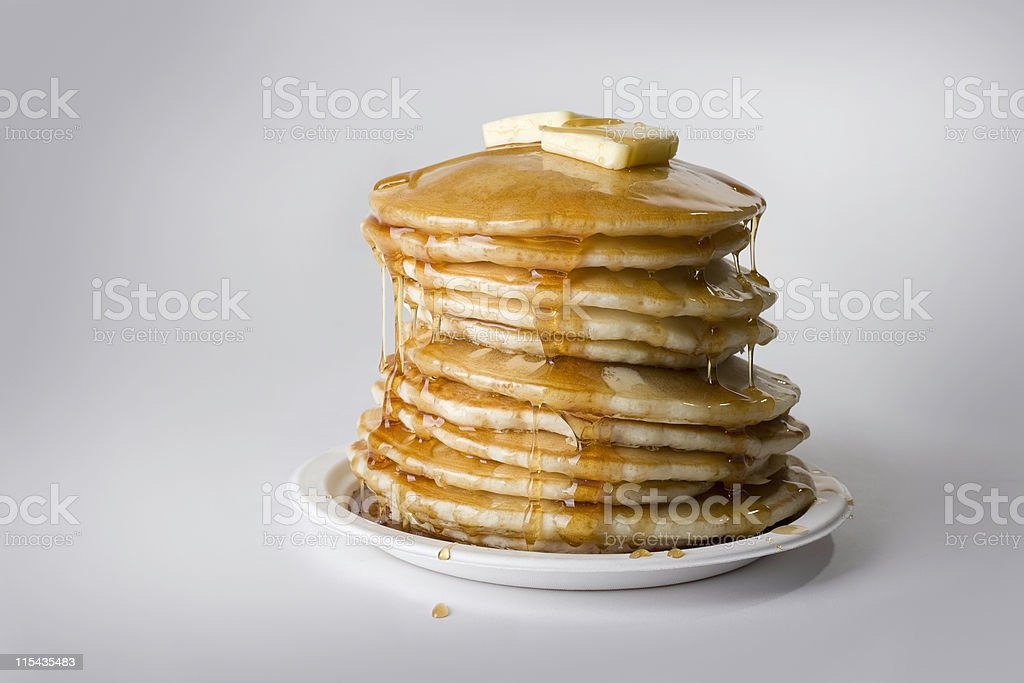 Precarious stack of pancakes with syrup and butter stock photo