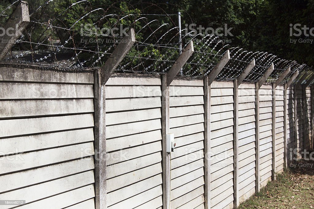 Precast Concrete Wall with Razor Sharp Barbed Security Wire stock photo