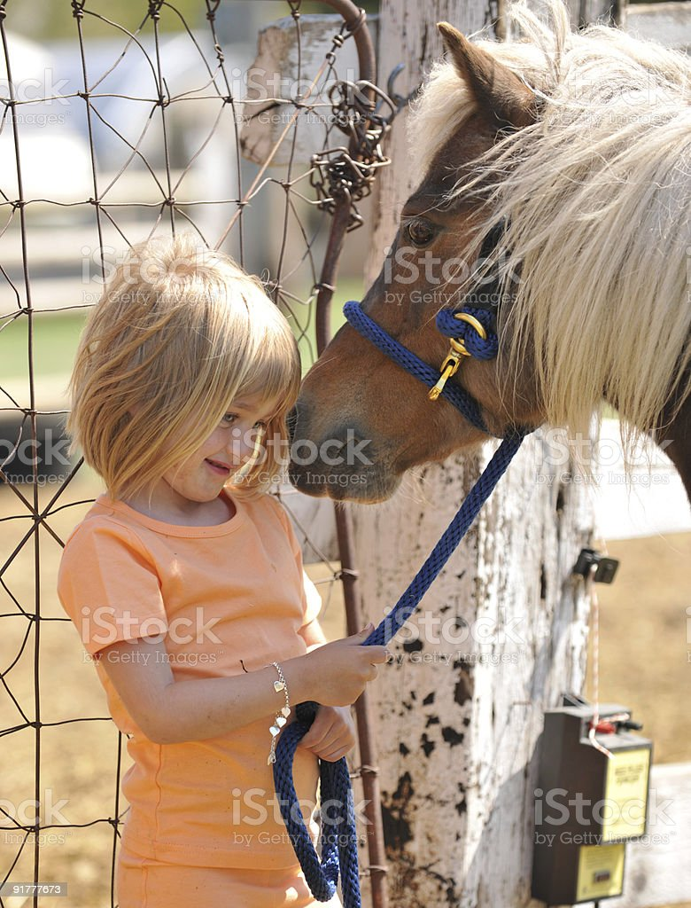Precious girl with her pony royalty-free stock photo