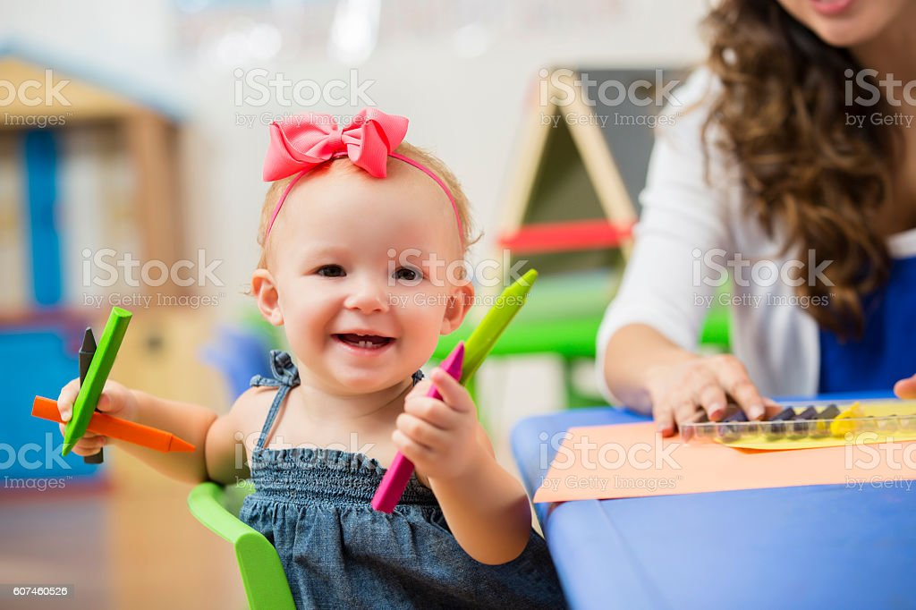 Precious happy toddler girl in preschool playing with crayons stock photo