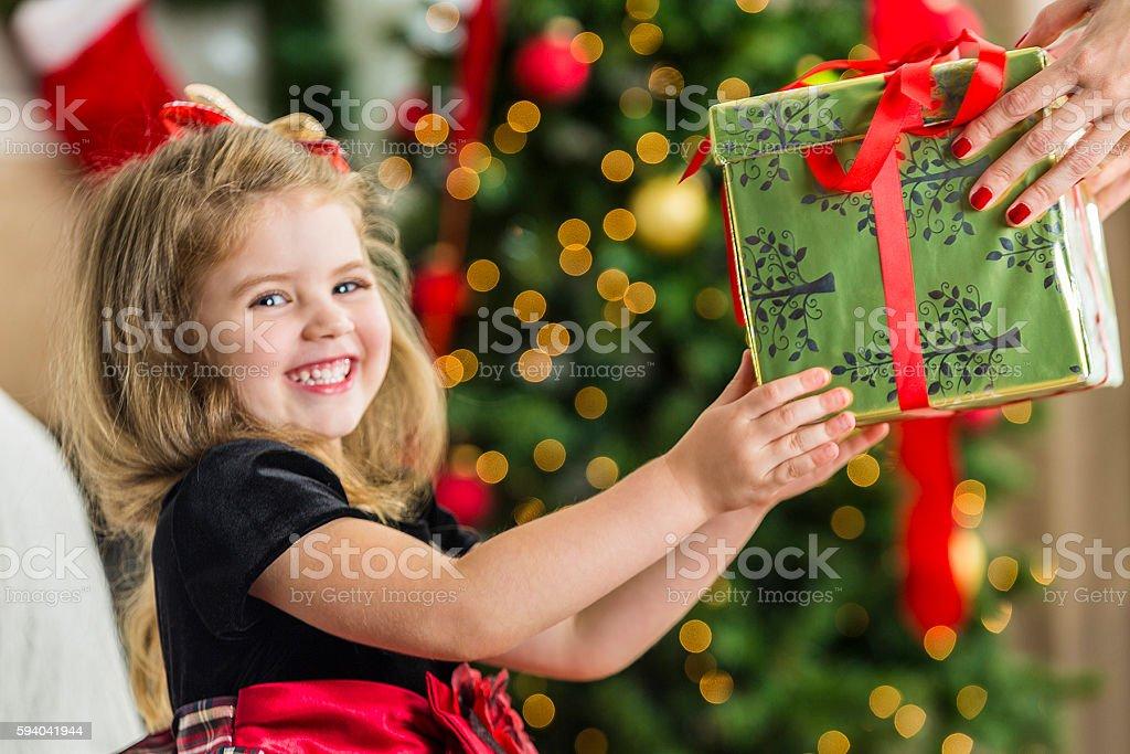 Precious little girl reaching for a Christmas present stock photo