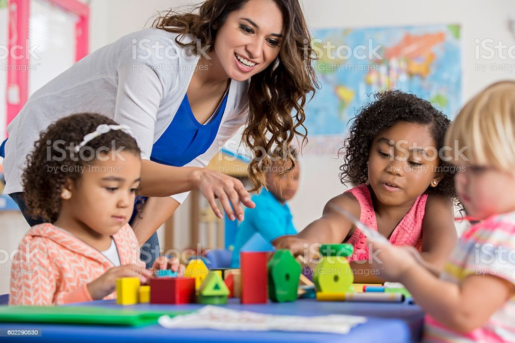 Precious preschool girls playing with building blocks at daycare stock photo