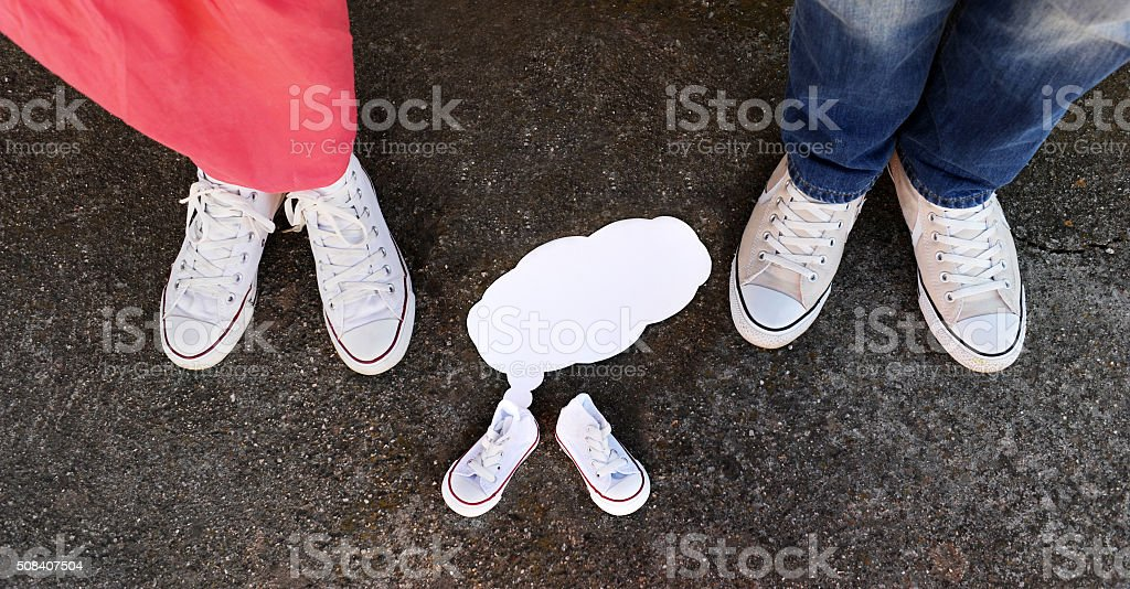 Pregnancy Announcement with Baby Shoes - Stock Image stock photo