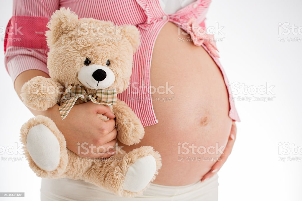 Pregnancy. Pregnant woman holding teddy bear toy in his hand stock photo