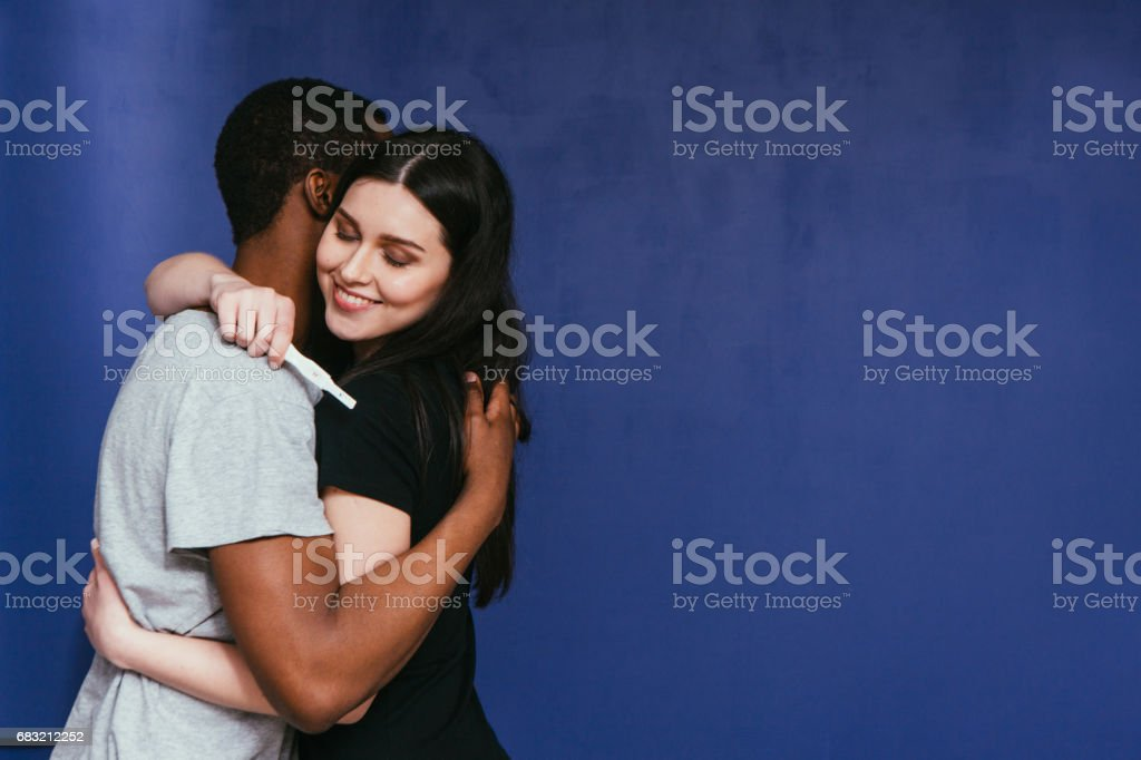 Pregnancy test, positive. Happy future parents hug stock photo