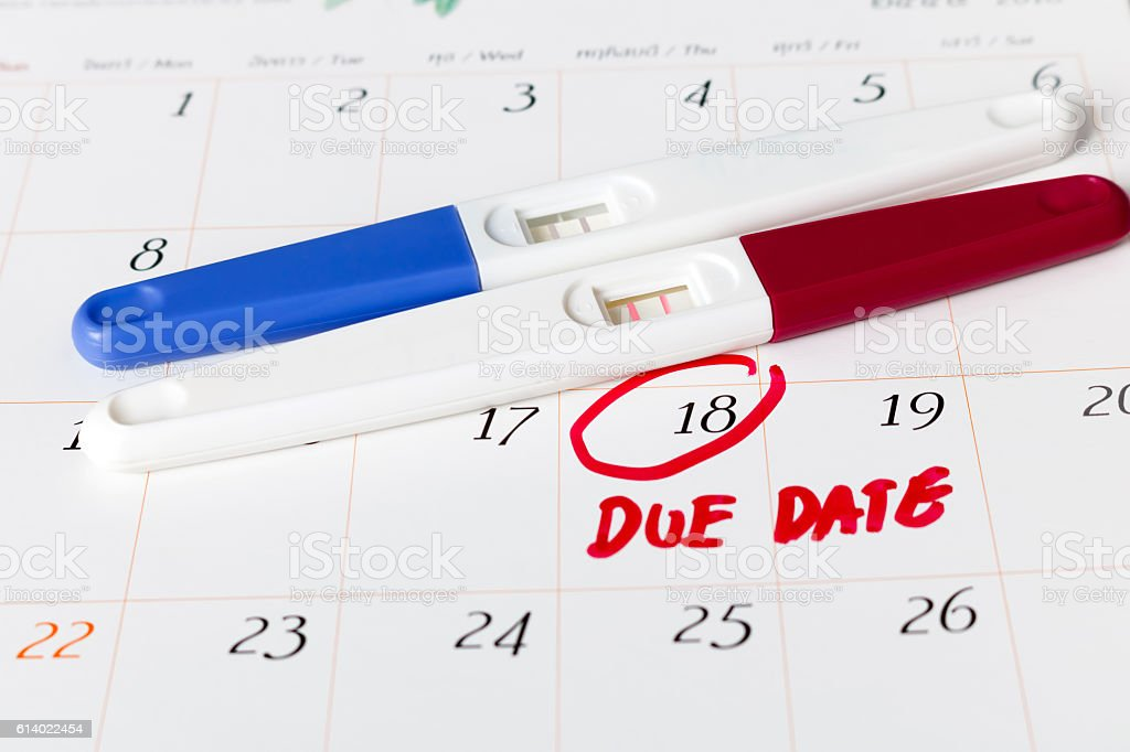 Pregnancy test with positive result lying on calendar background stock photo