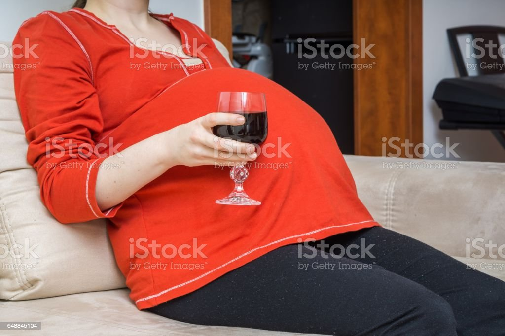 Pregnant alcoholic woman is drinking wine. stock photo