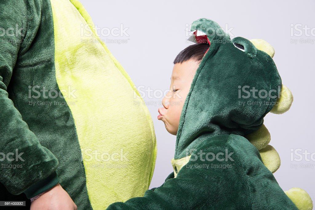 pregnant Asian mother and son acting dinosaur stock photo
