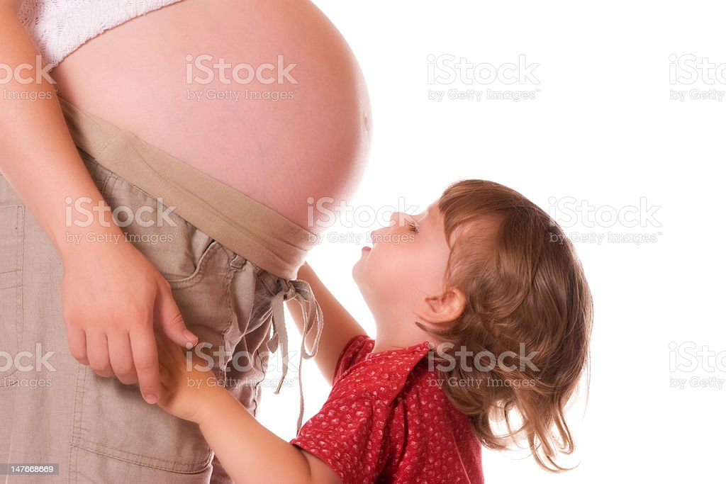 Pregnant belly and little girl stock photo