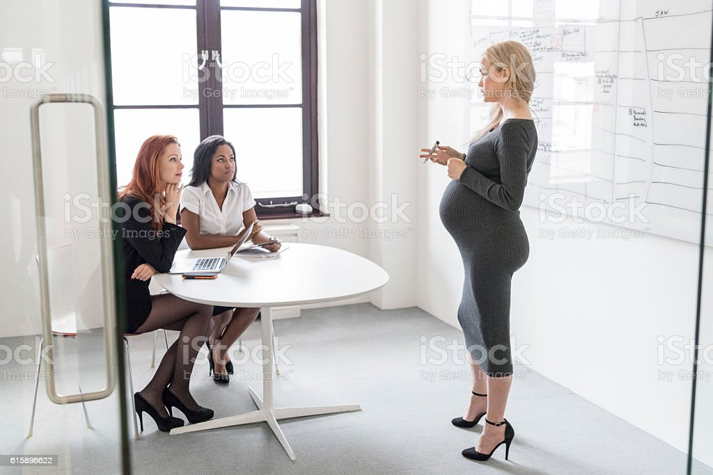 Pregnant businesswoman explaining to female colleagues in business meeting stock photo