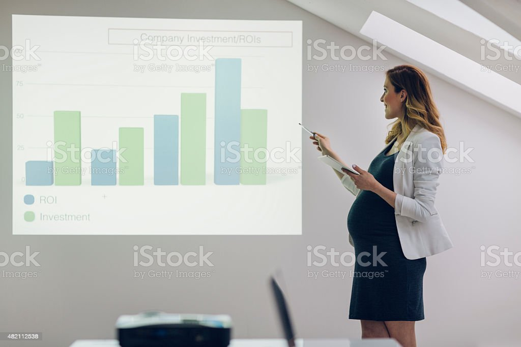 Pregnant Businesswoman Giving Presentation In Office. stock photo