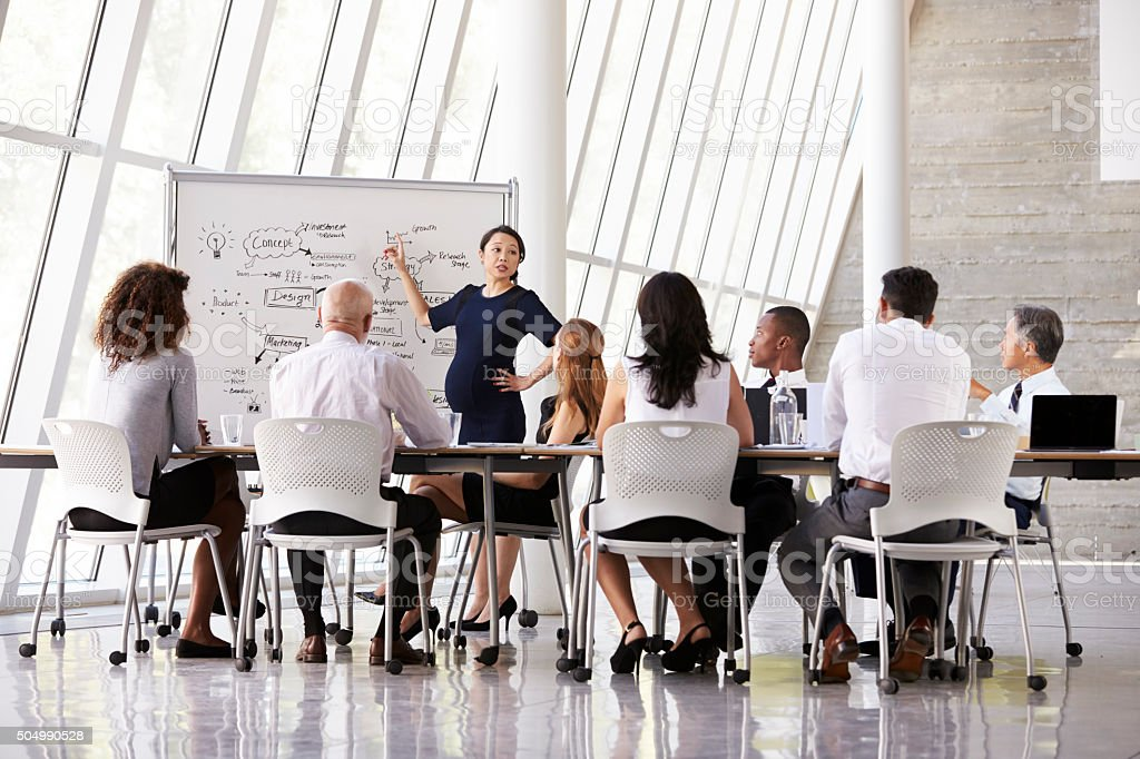 Pregnant Businesswoman Leads Boardroom Meeting stock photo