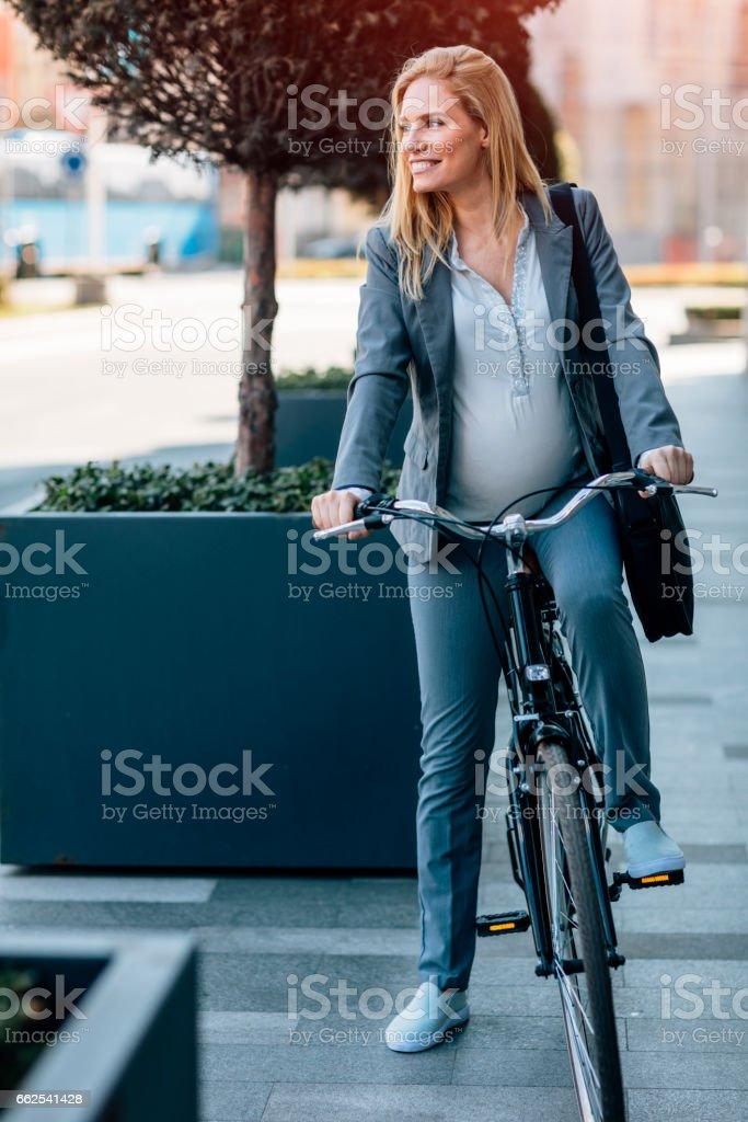 Pregnant Businesswoman Riding Bicycle stock photo