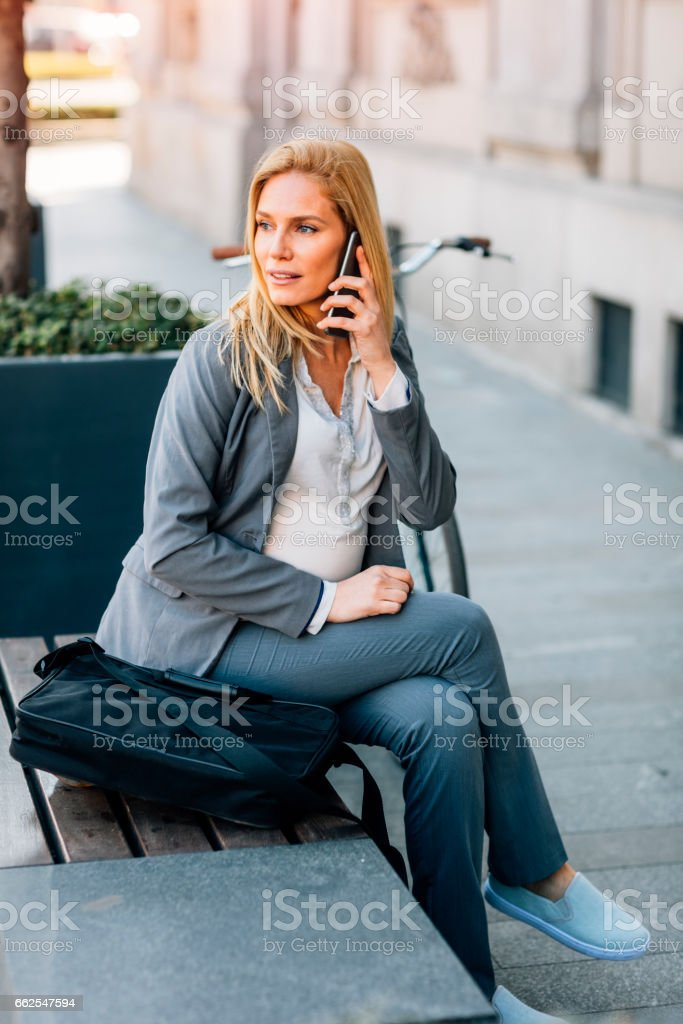 Pregnant Businesswoman using smart phone stock photo